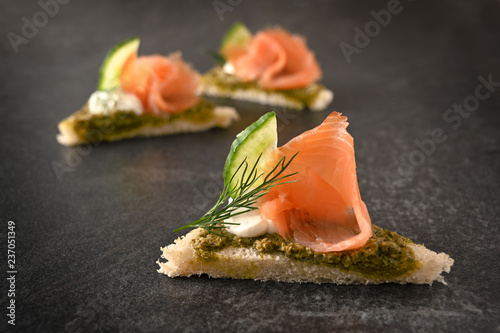 canapes with smoked salmon, cucumber, pesto, cream and dill garnish on dark stone with copy space, close up, selected focus, narrow depth of field