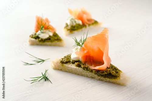 Fotobehang Buffet, Bar canapes with smoked salmon, pesto, cream and dill garnish on a light background with copy space