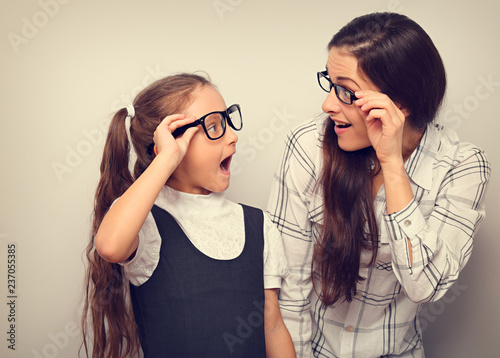 Happy surprising mother and excite kid in fashion glasses looking each other with opened mouth on empty copy space background. Vintage portrait