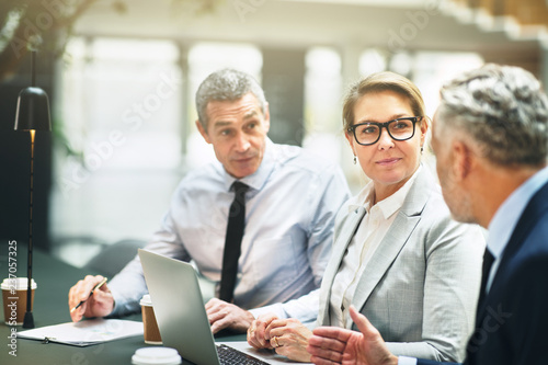 Fototapeta Three mature businesspeople having a meeting in an office lobby