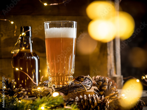 Tuinposter Bier / Cider Beer in glass on wooden background with Christmas lights and pine cones