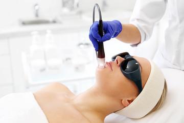 Zabieg laserowy na twarz. Kobieta w salonie kosmetycznym podczas zabiegu z użyciem lasera.