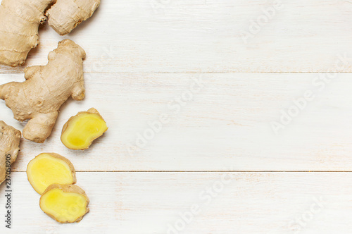 Foto op Plexiglas Kruiderij Whole and sliced fresh ginger roots on white wooden background top view copy space. Minimalistic style, seasoning, spice, ingredient for tea. Concept healthy food, medicine, improving immunity