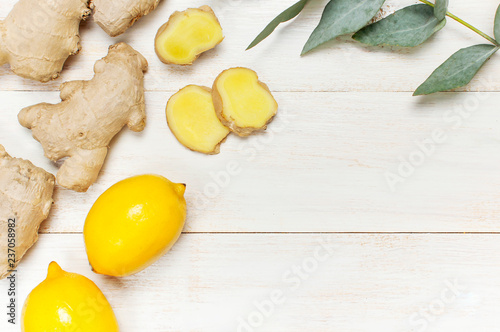 Tuinposter Kruiderij Whole and sliced fresh ginger roots, eucalyptus, lemon on white wooden background top view copy space. Seasoning, spice, ingredient for tea. Concept healthy food, medicine, improving immunity
