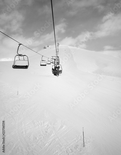 Chair-lift, snowy ski slope and cloudy sky with falling snow