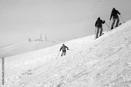 Skiers descent on snowy freeride slope and overcast misty sky