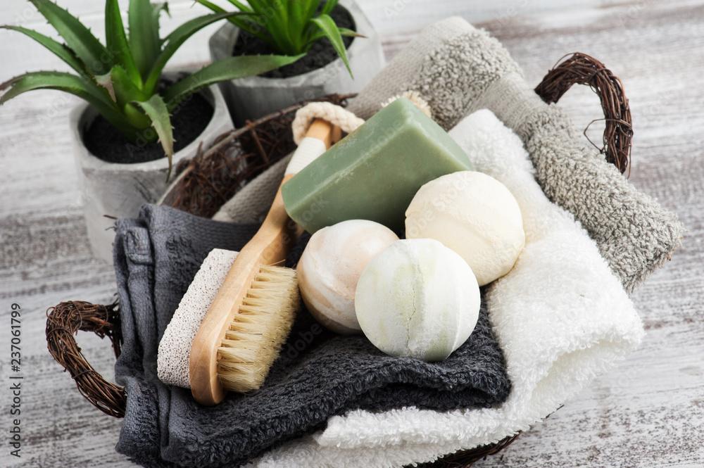 Fototapeta Folded towels in bascket with bath bombs