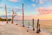 Lovers Key Beach In The Gulf Of Mexico, Florida Travel Destination. Woman Relaxing Watching Sunset Walking In Ocean Water On American Beach. Southwest Florida.