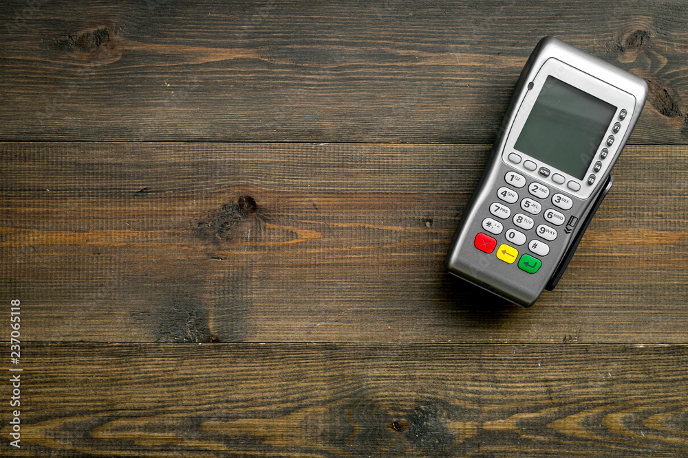Fototapeta Payment terminal, compact POS terminal on dark wooden background top view space for text