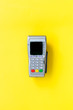 canvas print picture - Payment terminal, compact POS terminal on yellow background top view copy space
