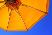 Looking Up Towards A Blue Sky Under A Yellow Sun Umbrella