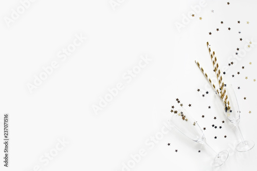 Happy New Year composition. Champagne glasses with golden confetti stars and drinking straws isolated on white table background. Celebration, party concept. Flat lay, top view. Empty copy space.