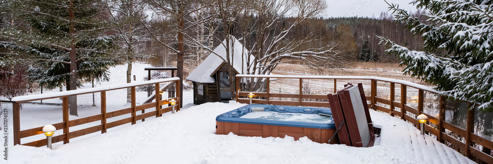 Fototapeta Panorama, outdoor Jacuzzi pool with fresh blue water in winter in Finland. Sauna and Finnish traditions.