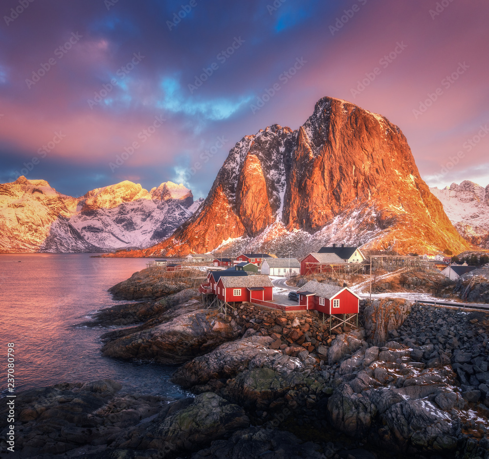 Fototapety, obrazy: Hamnoy village on the hill at sunrise. Lofoten islands, Norway. Winter landscape with houses, snowy mountains, sea, colorful sky with clouds. Norwegian traditional red rorbu and snow covered rocks