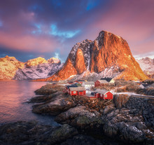 Hamnoy Village On The Hill At Sunrise. Lofoten Islands, Norway. Winter Landscape With Houses, Snowy Mountains, Sea, Colorful Sky With Clouds. Norwegian Traditional Red Rorbu And Snow Covered Rocks