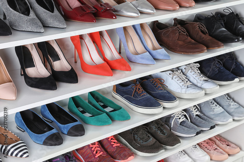 Shelving unit with different shoes. Element of dressing room interior