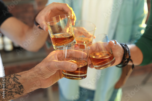 Friends toasting with glasses of whiskey indoors, closeup