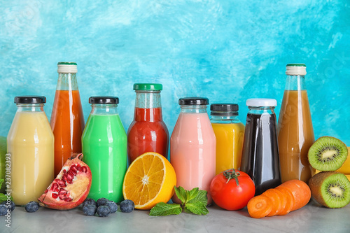 Bottles with different drinks and ingredients on table against color background