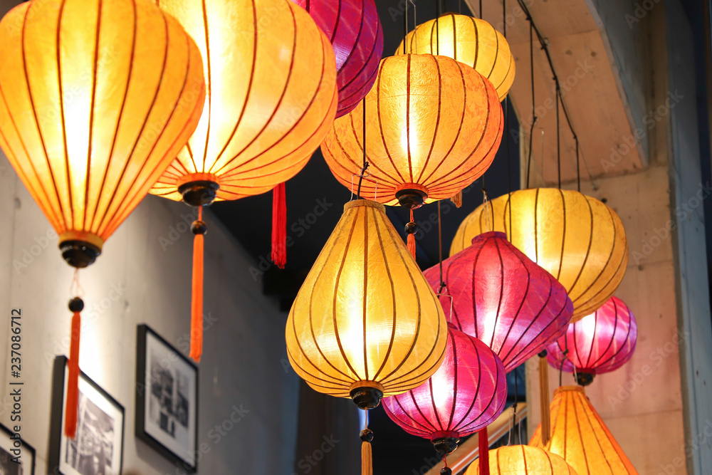 Yellow and pink lanterns hanged on wooden beam crating pretty interior decoration.