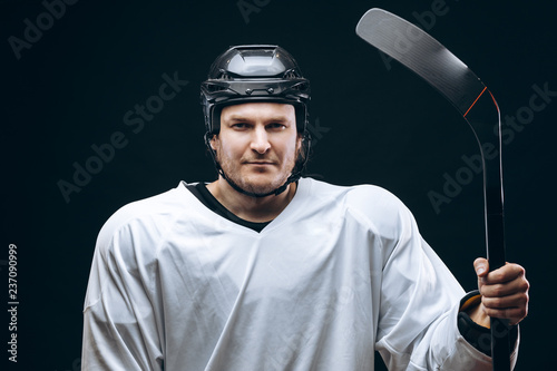 Professional caucasian hockey player holds hockey stick, looking at camera with decisive and confident look, the best team player, isolated on black