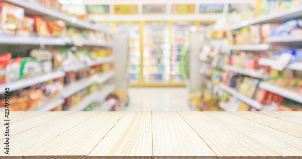 Fototapeta Wood table top with Supermarket convenience store aisle shelves interior blur for background