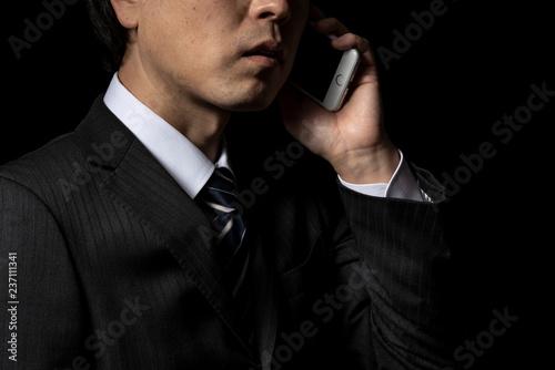 Fotografie, Obraz  スマートフォンで電話をかけるビジネスマン