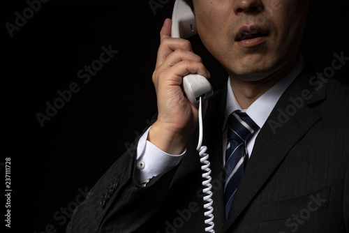 Fotografie, Obraz  電話で話をするスーツの男性