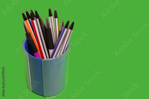 Fényképezés  set of new bright colored pens lying in a penholder on a green background