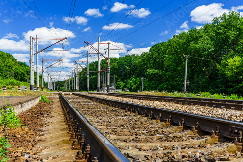 View on a railroad track and white clouds in blue sky