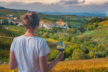 Girl Holding A Glass Of Red Wine Looking Amazing Green Vineyards In The Italian Region Of Piedmont, Alba, Barolo Town, Langhe Monferrato Region, Italy