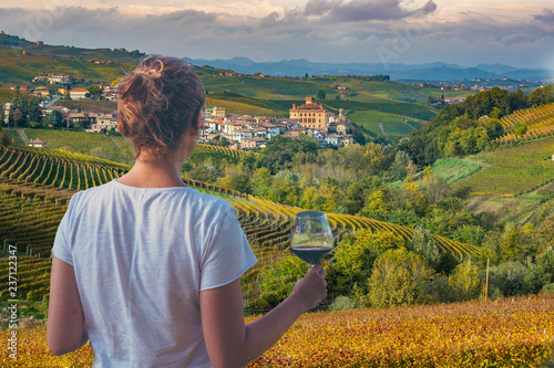 Photo girl holding a glass of red wine looking amazing green vineyards in the italian