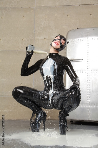 Fotografie, Tablou  hungry cat woman with mask helmet with a bottle of milk pours it over a black la