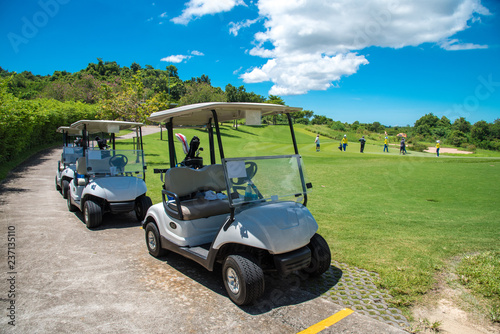 Golf carts parking near golf course with golfers and caddie are in competition,blue cloud sky background. - 237135110