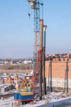 Lifting Equipment. Crawler Cranes, Piles, Concrete Slabs And Cranes On The Construction Site Near The Multi-storey Building. The Process Of Driving Piles.