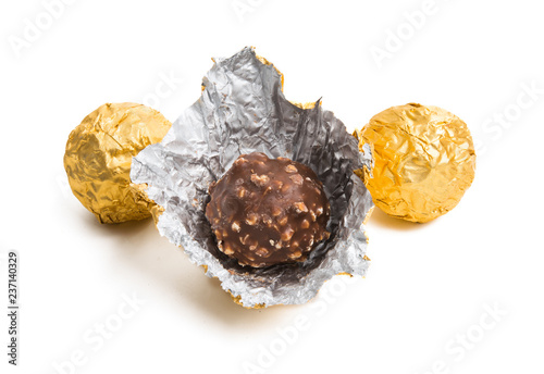 Fotografía  chocolate candy in golden foil isolated