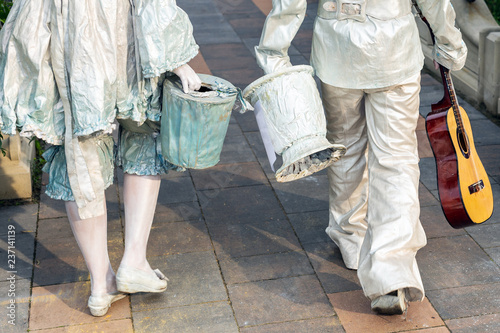 Fotografia  Pair of street artist painted in white silver paint walking in city park