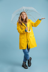 Full length image of blonde woman 20s wearing yellow raincoat standing under transparent umbrella, isolated over blue background