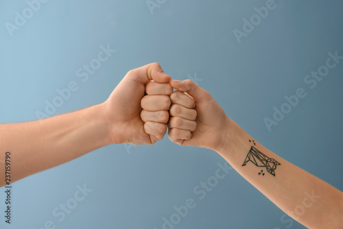 Fototapeta Man and woman bumping fists on color background