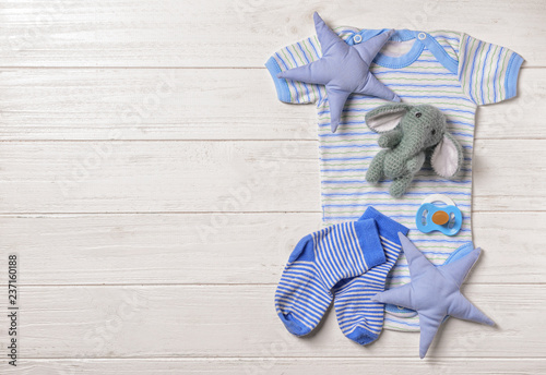 Fotografie, Obraz  Set of baby clothes and accessories on white wooden background, flat lay