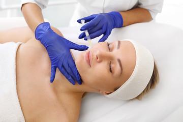 Wypełnianie zmarszczek kwasem hialuronowym. Pacjentka w klinice kosmetycznej, kosmetyczka wykonuje zabieg ostrzykiwania.