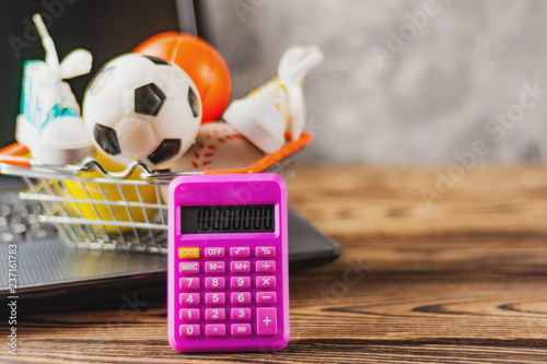 Sports Equipment In Market Basket On Old Dirty Laptop And Calculator Brown Table Online Trade Concept
