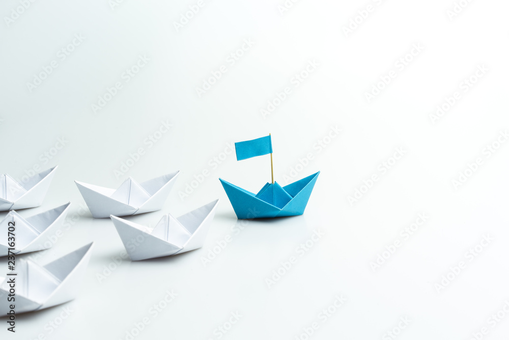 Fototapeta Leadership concept, blue paper ship leading among white on white background.