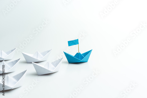Obraz na płótnie Leadership concept, blue paper ship leading among white on white background