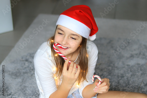 6421e6d5f22f9 Beautiful happy preteen girl in red Santa Claus hat eating striped Christmas  candy canes holding sweets