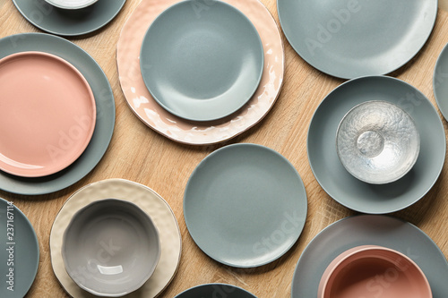 Set of clean tableware on wooden background, top view