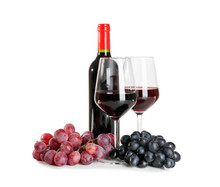 Glasses And Bottle Of Red Wine With Ripe Grapes On White Background