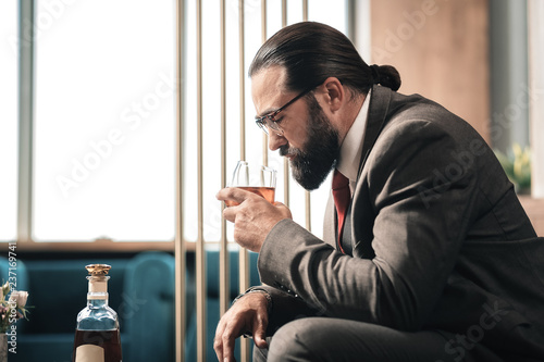 Foto  Bearded dark-haired man smelling expensive quality cognac