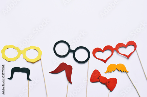 Props for party. Carnival accessories set. Paper glasses, hat, lips, moustaches, tie on wooden sticks.