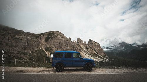 Obraz na plátně  G-Wagon in Italy standing beside the road with mountains