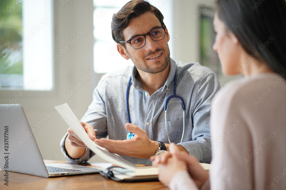 Fototapeta  Modern young doctor speaking to patient in office